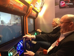 Richard Branson playing on our Grid Twin Deluxe arcade racing game